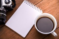 Coffee cup top view and camera and notebook on wooden vintage table background Stock Photo