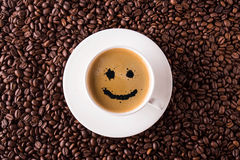 Coffee cup top view with smile. On coffee beans Royalty Free Stock Photo