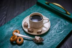 Coffee cup with coffee on a tray. The tray stands on a black wooden background. Next to a cup of coffee sugar with cinnamon, tea spoon and bagels stock photos