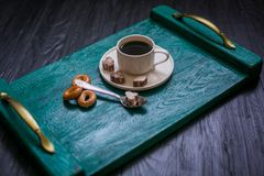 Coffee cup with coffee on a tray. The tray stands on a black wooden background. Next to a cup of coffee sugar with cinnamon, tea spoon and bagels stock image