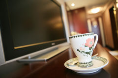 Coffee cup beside TV. Coffee cup with flower beside TV Royalty Free Stock Photography