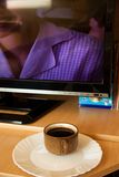 Coffee cup beside tv Stock Image