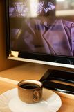 Coffee cup beside tv Royalty Free Stock Images