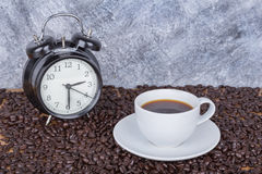 Coffee in cup and vintage clock Coffee time concept with wall Stock Image
