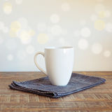 Coffee cup on vintage table over bokeh background Royalty Free Stock Images