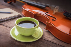 Coffee cup with violin and book on wooden table Stock Photo