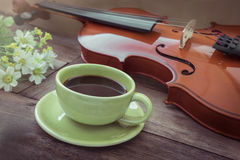 Coffee cup and violin on wooden table, filtered image Stock Images