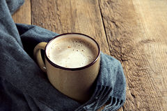 Coffee cup and warm scarf. On old rustic wooden table with copy space Stock Image