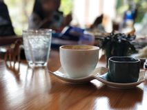 Coffee cup and water glass on the wooden table. stock photo