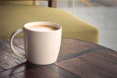 Coffee Cup. White coffee cup on brown table with sofa at coffee shop Royalty Free Stock Photography