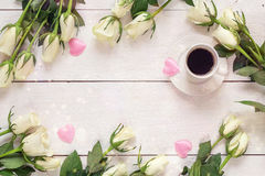 Coffee cup and white rose flowers on white table background.  To Royalty Free Stock Photo