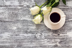 Coffee cup and white rose flowers on wooden table background. To Royalty Free Stock Photography