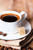 Coffee cup with white saucer and roasted coffee beans  on wooden Royalty Free Stock Image