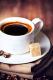 Coffee cup with white saucer and roasted coffee beans  on wooden Royalty Free Stock Photos