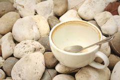 Coffee cup wih tea spoon on stone background. Stock Photo