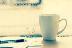 Coffee cup beside window Stock Image