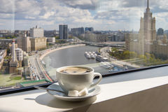 Coffee Cup on windowsill with city view. Cup of coffee on the windowsill in a tall building overlooking the city from the river Stock Photography