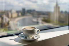 Coffee Cup on windowsill with city view. Cup of coffee on the windowsill in a tall building overlooking the city from the river Stock Photo