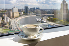 Coffee Cup on windowsill with city view. Cup of coffee on the windowsill in a tall building overlooking the city from the river Stock Images