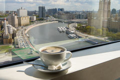Coffee Cup on windowsill with city view. Cup of coffee on the windowsill in a tall building overlooking the city from the river Royalty Free Stock Photo