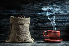 Coffee Cup With Steam And Sack Of Beans Stock Photography