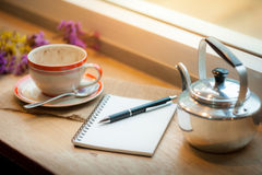 Coffee cup on wood bar in cafe. Opened notebook, pen and coffee cup on wood bar in coffee shop in afternoon time royalty free stock photos