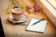 Coffee cup on wood bar in cafe. Coffee cup, opened notebook, and pen on wood bar beside window at coffee shop in afternoon time royalty free stock photos