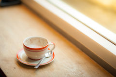 Coffee cup on wood bar in cafe. Coffee cup on wood bar beside window at coffee shop in afternoon time royalty free stock photography