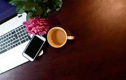Coffee cup on wood desk with laptop and mobile phone Stock Image