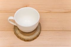 Coffee cup on the wood plate. Little coffee cup on the wood plate over the brown background royalty free stock photo