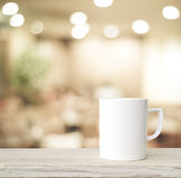 Coffee cup on wood table over blurred cafe  background Stock Photography