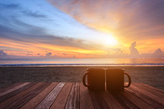Coffee cup on wood table at sunset or sunrise beach Stock Photography