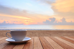 Coffee cup on wood table at sunset or sunrise beach Stock Photos