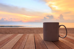 Coffee cup on wood table at sunset or sunrise beach Royalty Free Stock Photos