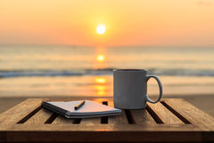 Coffee cup on wood table at sunset or sunrise beach. Close up coffee cup on wood table at sunset or sunrise beach Royalty Free Stock Images
