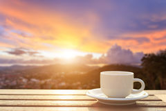 Coffee cup on wood table at sunset or sunrise time Royalty Free Stock Photos