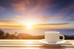 Coffee cup on wood table at sunset or sunrise time Royalty Free Stock Photo