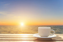 Coffee cup on wood table at sunset or sunrise time Stock Photo