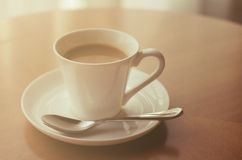 Coffee cup on wood table. With vintage blur filter effect stock image