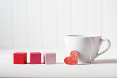 Coffee cup with wooden blocks. Coffee cup with small heart with wooden blocks Stock Images