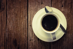 Coffee cup on wooden. Close up overhead view of a cup of strong frothy espresso coffee on a rough textured wooden surface with dark vignetting and a highlight Royalty Free Stock Image