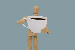 Coffee cup. Wooden dummy holding a oversized cup of black coffee   on blue background Stock Photography