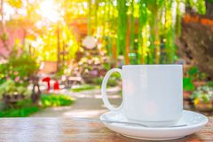 Coffee cup on wooden table green outdoor nature stock images