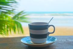 Coffee cup. On wooden table in morning time with blurred sea landscape background Stock Images