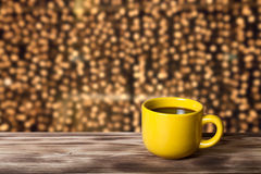 Coffee in cup on wooden table opposite a blurred background Stock Images