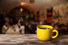 Coffee in cup on wooden table opposite a blurred background Royalty Free Stock Photos