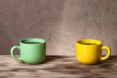 Coffee in cup on wooden table opposite a defocused burlap backgr Royalty Free Stock Photo