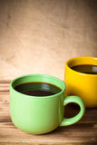 Coffee in cup on wooden table opposite a defocused burlap backgr Stock Photography