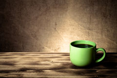 Coffee in cup on wooden table opposite a defocused burlap backgr Stock Photo