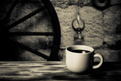 Coffee in cup on wooden table opposite defocused vintage backgro Royalty Free Stock Photo